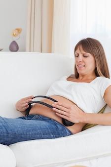 Retrato de uma mulher grávida com fones de ouvido na barriga