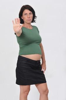 Retrato de uma mulher grávida com uma placa de pare no fundo branco