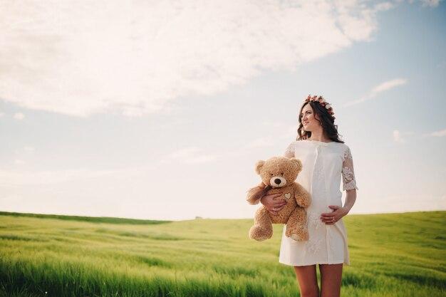 Retrato de uma mulher gravida com urso de peluche à disposição no campo da grama.