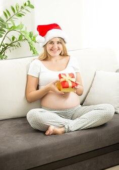 Retrato de uma mulher grávida feliz olhando para dentro da caixa de presente de natal