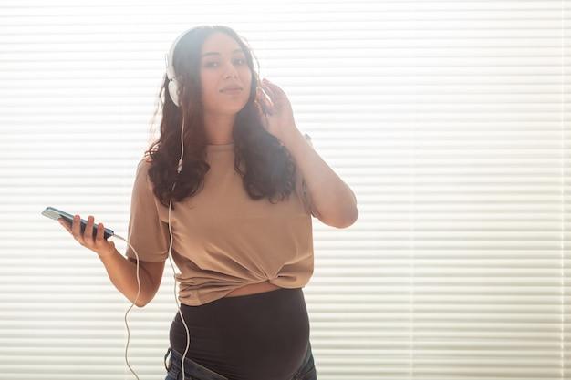 Retrato de uma mulher grávida perto de uma janela em casa e ouvindo música em fones de ouvido com espaço de cópia. conceito de gravidez e lazer.