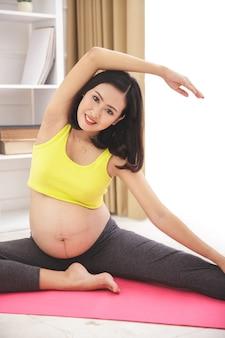 Retrato de uma mulher grávida saudável e feliz fazendo alongamento para ioga