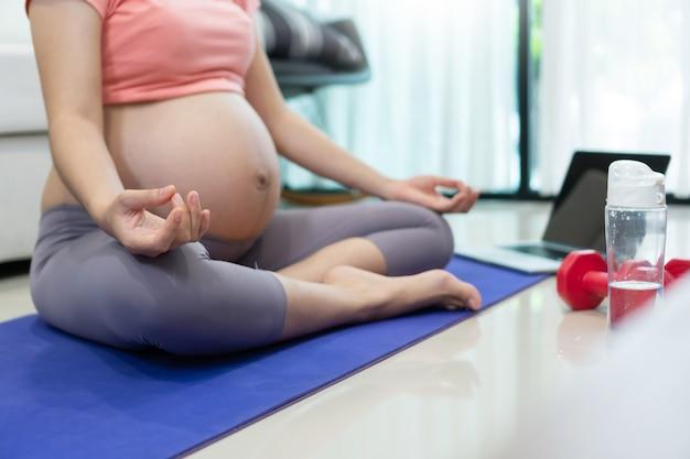 Retrato de uma mulher grávida sentada fazendo exercícios de ioga em posição de lótus