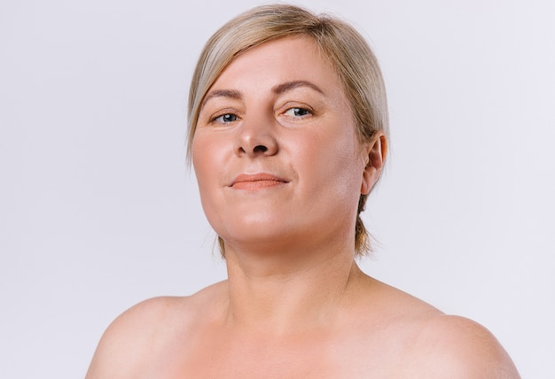Retrato de uma mulher idosa com pele limpa e natural, olhando para a câmera em um fundo branco. foto de alta qualidade