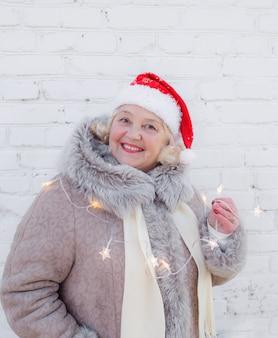 Retrato de uma mulher idosa com um chapéu de papai noel vermelho