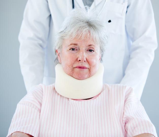 Retrato de uma mulher idosa com uma cinta de pescoço sentado em uma cadeira de rodas