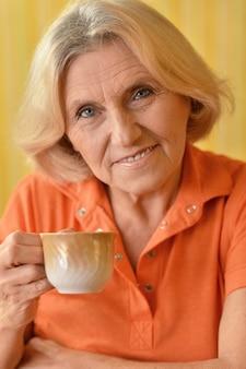 Retrato de uma mulher idosa com uma xícara em casa