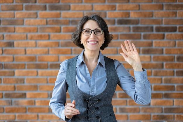 Retrato de uma mulher idosa elegante caucasiana sorridente com óculos, tendo uma videoconferência agradável usando a webcam do computador laptop, sorrindo