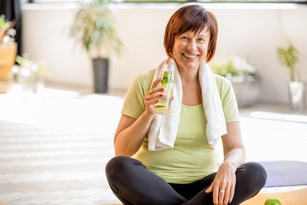 Retrato de uma mulher idosa em roupas esportivas bebendo água após o exercício dentro de casa, em casa ou na academia