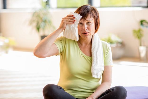 Retrato de uma mulher idosa em roupas esportivas, descansando após o exercício dentro de casa, em casa ou na academia