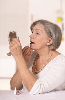 Retrato de uma mulher idosa feliz em casa se olhando no espelho