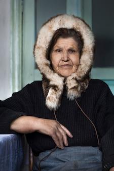 Retrato de uma mulher idosa no chapéu do inverno da pele. os habitantes do norte.