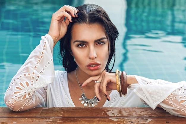 Retrato de uma mulher incrível e sensual com corpo bronzeado perfeito, posando na piscina