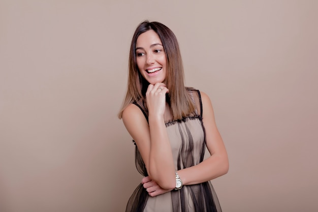 Retrato de uma mulher interessada com cabelo escuro curto e sorriso encantador vestida de vestido bege, posando na parede bege, lugar para texto, parede isolada