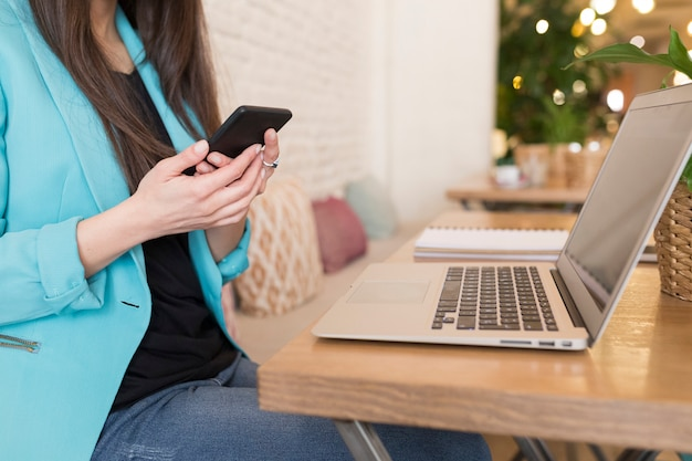Retrato de uma mulher irreconhecível usando telefone celular em um restaurante. vida moderna de um blogueiro com computador laptop, tablet, notebook e café na mesa. roupas casuais. estilo de vida