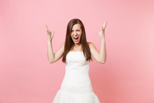 Retrato de uma mulher irritada com raiva em um lindo vestido branco em pé gritando, espalhando as mãos
