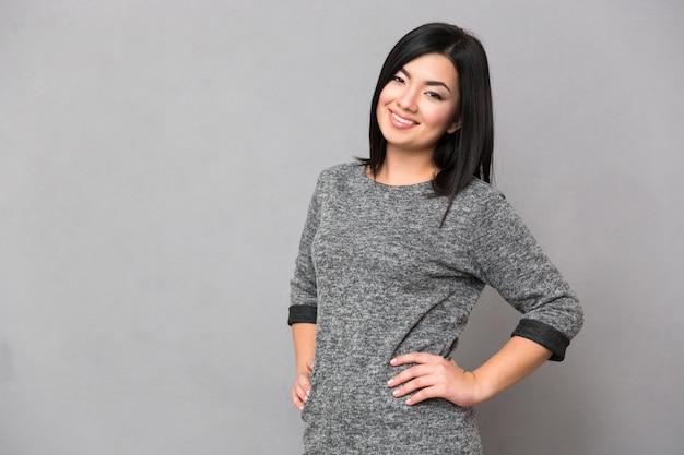 Retrato de uma mulher japonesa feliz olhando para a frente sobre uma parede cinza