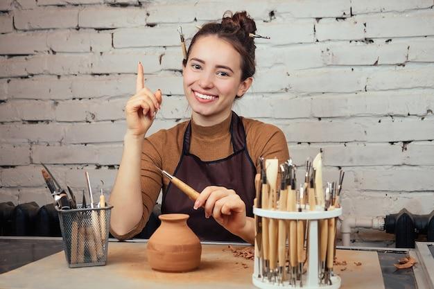 Retrato de uma mulher jovem e alegre, segurando um vaso de barro. o oleiro faz um vaso à mesa de uma olaria. conceito de inspiração e ideias