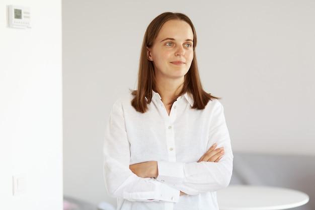 Retrato de uma mulher jovem e atraente adulta com cabelos escuros, vestindo uma camisa branca estilo casual, em pé com os braços cruzados, olhando para longe com uma expressão confiante.