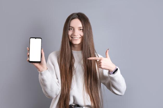 Retrato de uma mulher jovem e atraente com cabelo comprido escuro, facilmente sorrindo e aponta o dedo para um smartphone de telefone celular em branco sobre um fundo cinza do estúdio. lugar para texto. com espaço de cópia.