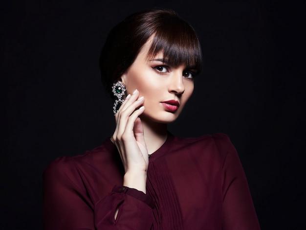 Retrato de uma mulher jovem e bonita contra um fundo escuro.