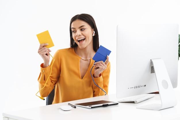 Retrato de uma mulher jovem e bonita designer usando um computador tablet gráfico e segurando dispositivos de armazenamento de dados enquanto trabalhava em um escritório luminoso