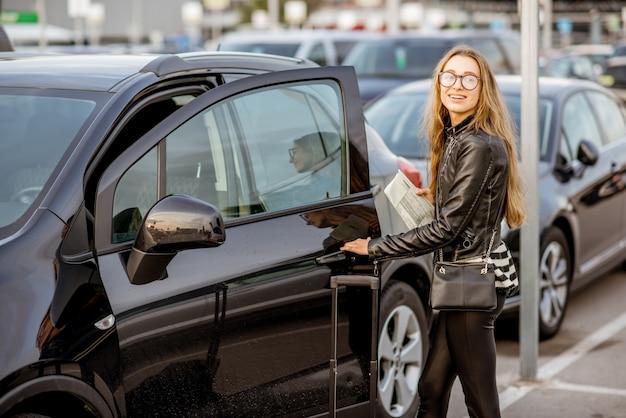 Retrato de uma mulher jovem e feliz abrindo a porta do carro alugado ao ar livre no estacionamento