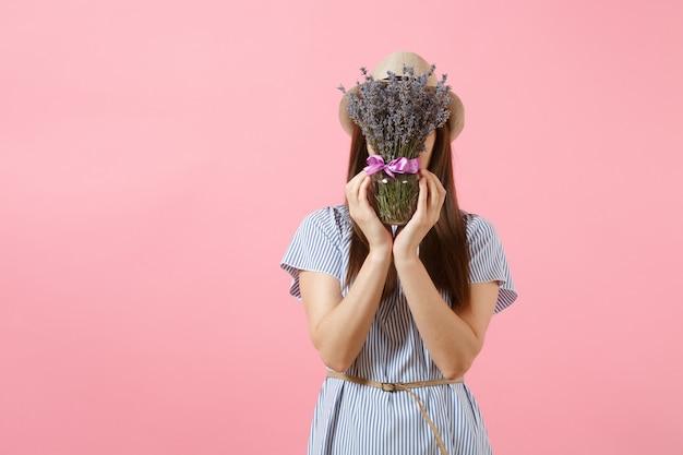 Retrato de uma mulher jovem e feliz concurso em vestido azul, chapéu segurando o buquê de flores de lavanda roxas lindas isoladas em um fundo rosa tendência brilhante. conceito de feriado do dia internacional da mulher.