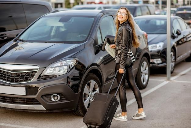 Retrato de uma mulher jovem e feliz viajando com a mala perto do carro alugado ao ar livre no estacionamento