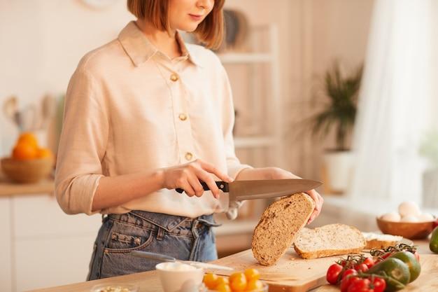 Retrato de uma mulher jovem e moderna cortando pão integral fresco enquanto prepara o café da manhã em uma cozinha aconchegante