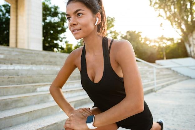 Retrato de uma mulher jovem fitness em fones de ouvido