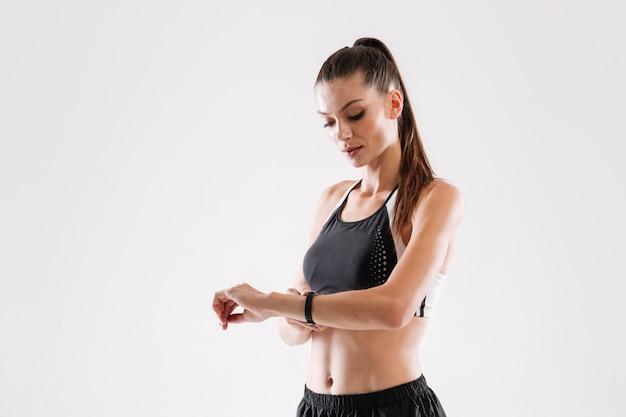 Retrato de uma mulher jovem fitness olhando para o relógio de pulso