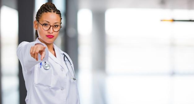 Retrato de uma mulher jovem médico negro alegre e sorridente apontando para a frente
