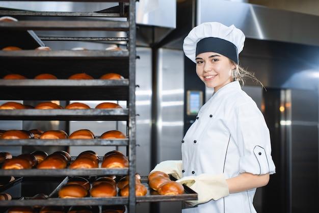 Retrato de uma mulher jovem padeiro com forno industrial com bolos em uma padaria