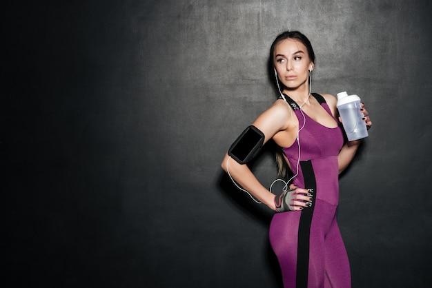 Retrato de uma mulher jovem saudável fitness segurando a garrafa de água