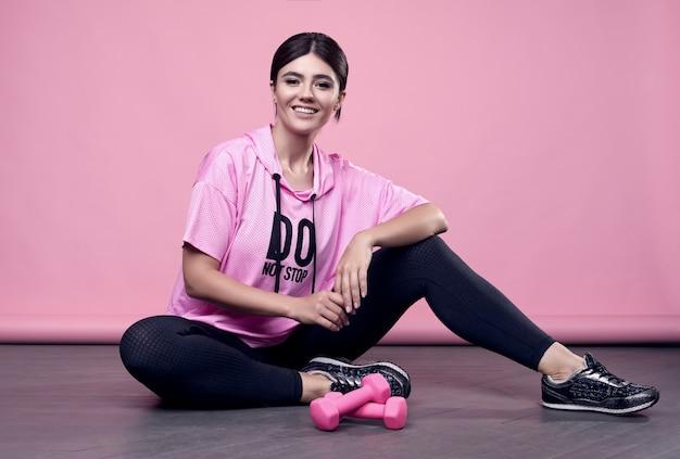 Retrato de uma mulher latina positiva de corpo lindo em um capuz rosa esportes exercitar com halteres em rosa