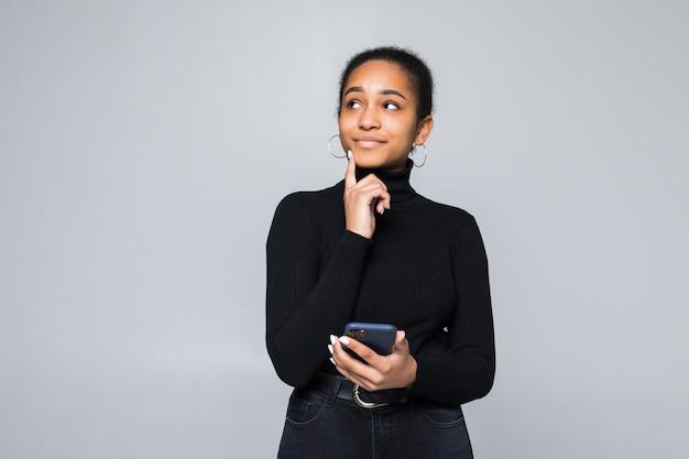 Retrato de uma mulher latina, segurando o telefone móvel e desviar o olhar com a mão no queixo