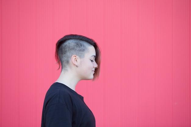 Retrato de uma mulher lésbica adolescente em uma parede rosa