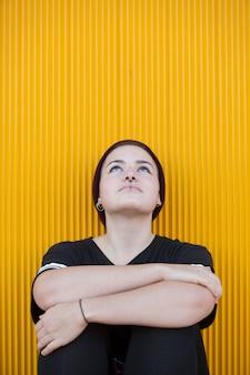 Retrato de uma mulher lésbica adolescente pensativa em uma parede amarela