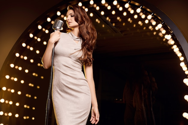 Retrato de uma mulher linda cantora em um vestido elegante com microfone retrô nos refletores de palco do restaurante.