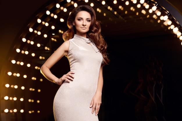 Retrato de uma mulher linda cantora em um vestido elegante, posando nos holofotes do palco do restaurante.
