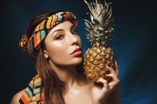 Retrato de uma mulher linda com bandana colorida na cabeça, segurando o abacaxi.