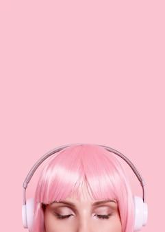 Retrato de uma mulher linda com cabelo rosa curtindo música em fones de ouvido