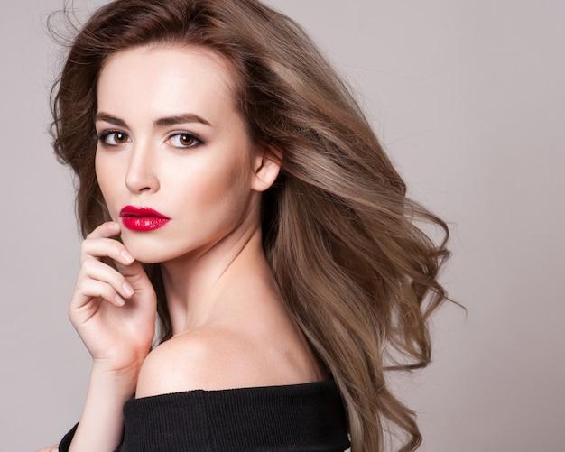 Retrato de uma mulher linda com penteado encaracolado e maquiagem brilhante