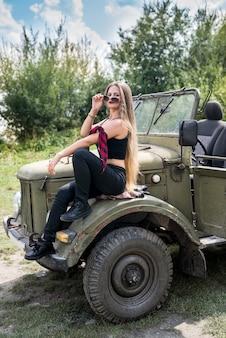 Retrato de uma mulher linda de cabelos longos sentada no capô do carro