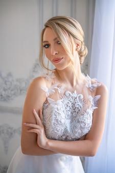 Retrato de uma mulher linda em um vestido de noiva branco com uma bela maquiagem e penteado