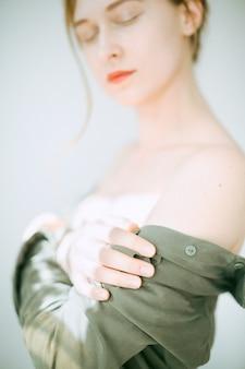Retrato de uma mulher linda na sala de pé e pensando com os olhos fechados em vestido verde