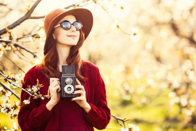 Retrato de uma mulher linda ruiva de suéter vermelho e chapéu com câmera no jardim de macieira flor na primavera no pôr do sol.