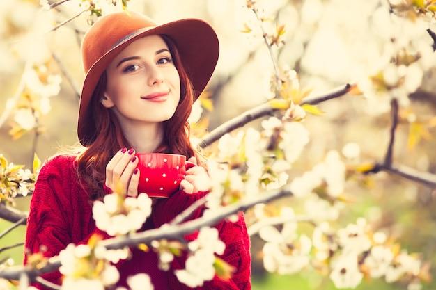 Retrato de uma mulher linda ruiva de suéter vermelho e chapéu com copa no jardim flor macieira na primavera no pôr do sol.