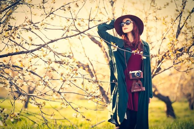 Retrato de uma mulher linda ruiva na capa e chapéu com câmera no jardim de macieira flor na primavera no pôr do sol.